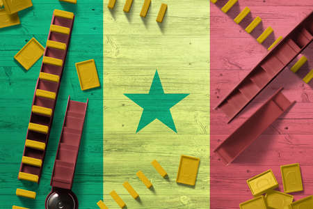Senegal flag with national background with dominoes on wooden table. Top view. Concept of game.