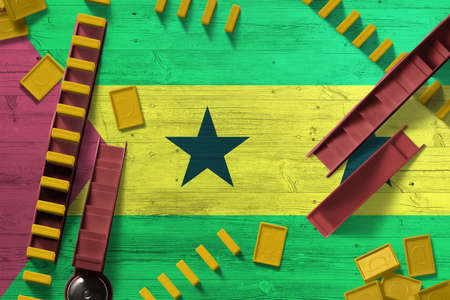 Sao Tome And Principe flag with national background with dominoes on wooden table. Top view. Concept of game.