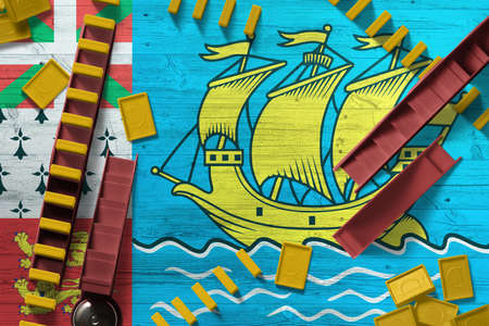 Saint Pierre And Miquelon flag with national background with dominoes on wooden table. Top view. Concept of game.