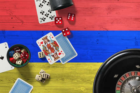 Armenia casino theme. Aces in poker game, cards and chips on red table with national wooden flag background. Gambling and betting.