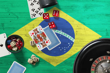 Brazil casino theme. Aces in poker game, cards and chips on red table with national wooden flag background. Gambling and betting. Stockfoto