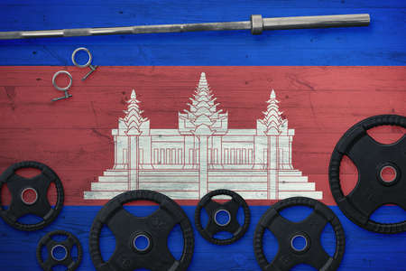 Cambodia gym concept. Top view of heavy weight plates with iron bar on national background.