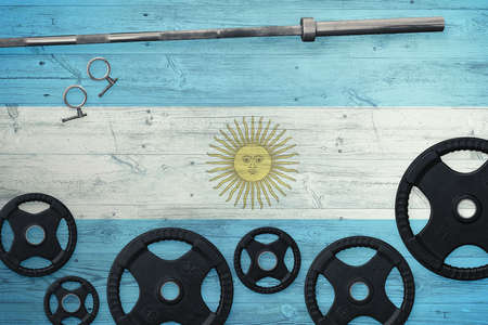 Argentina gym concept. Top view of heavy weight plates with iron bar on national background.