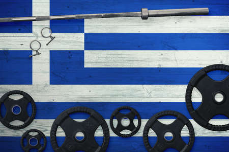Greece gym concept. Top view of heavy weight plates with iron bar on national background.