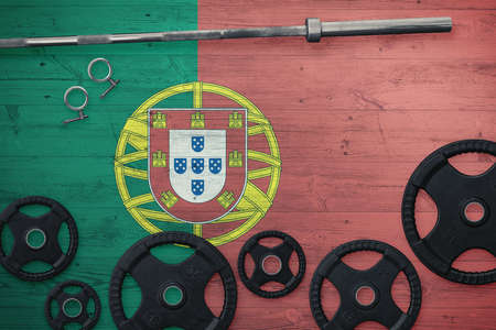 Portugal gym concept. Top view of heavy weight plates with iron bar on national background.