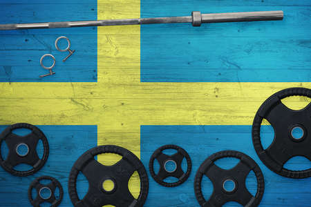 Sweden gym concept. Top view of heavy weight plates with iron bar on national background. Standard-Bild