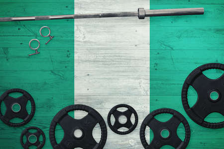 Nigeria gym concept. Top view of heavy weight plates with iron bar on national background.