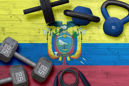 Ecuador sports club concept. Top view of heavy weight plates with iron bar on national background.