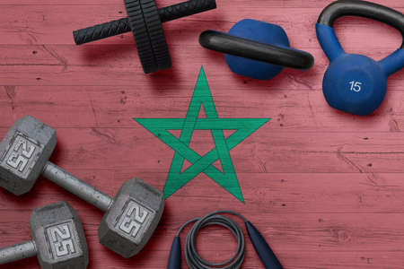 Morocco sports club concept. Top view of heavy weight plates with iron bar on national background.