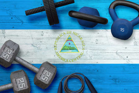 Nicaragua sports club concept. Top view of heavy weight plates with iron bar on national background.
