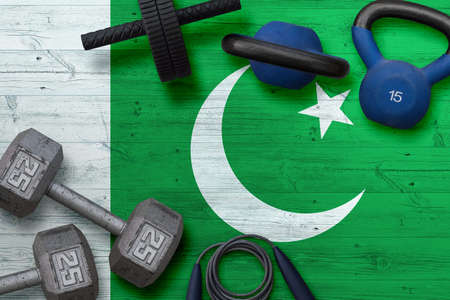 Pakistan sports club concept. Top view of heavy weight plates with iron bar on national background.