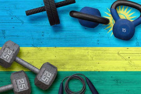 Rwanda sports club concept. Top view of heavy weight plates with iron bar on national background.