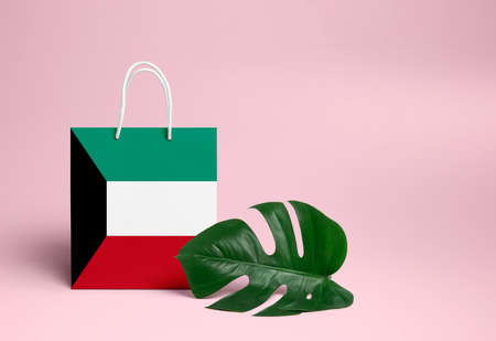 Kuwait shopping concept. National cardboard shopping bag with monstera leaf and pink background. Online shopping theme.
