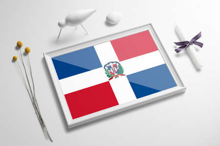 Dominican Republic flag in wooden frame on table. White natural soft concept, national celebration theme.