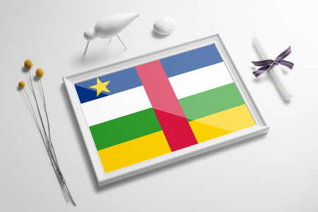 Central African Republic flag in wooden frame on table. White natural soft concept, national celebration theme.