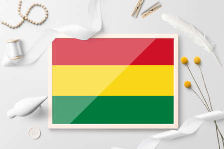 Bolivia flag in wooden frame on white creative background. White theme, feather, daisy, button, ribbon objects.