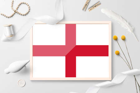 England flag in wooden frame on white creative background. White theme, feather, daisy, button, ribbon objects.