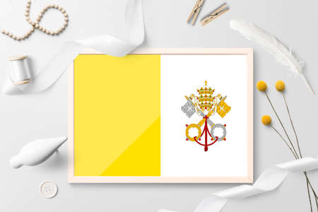 Vatican City flag in wooden frame on white creative background. White theme, feather, daisy, button, ribbon objects.