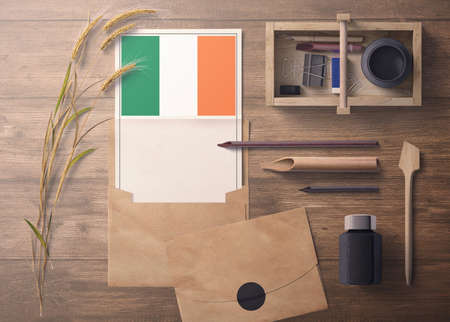 Ireland invitation, celebration letter concept. Flag with craft paper and envelope. Retro theme with divide, ink, wooden pen objects.