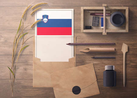 Slovenia invitation, celebration letter concept. Flag with craft paper and envelope. Retro theme with divide, ink, wooden pen objects.