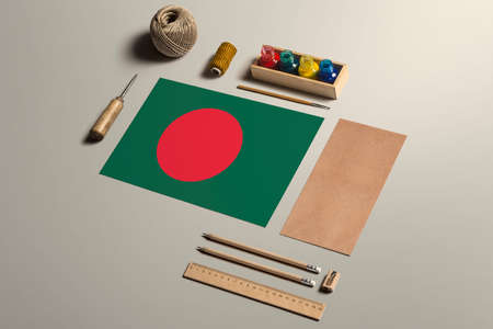 Bangladesh calligraphy concept, accessories and tools for beautiful handwriting, pencils, pens, ink, brush, craft paper and cardboard crafting on wooden table.