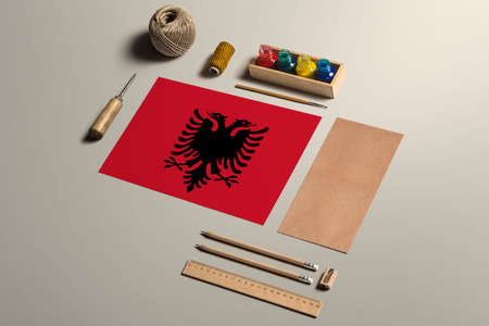 Albania calligraphy concept, accessories and tools for beautiful handwriting, pencils, pens, ink, brush, craft paper and cardboard crafting on wooden table.