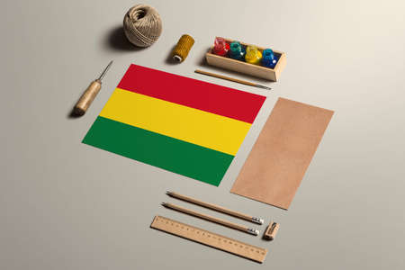 Bolivia calligraphy concept, accessories and tools for beautiful handwriting, pencils, pens, ink, brush, craft paper and cardboard crafting on wooden table.
