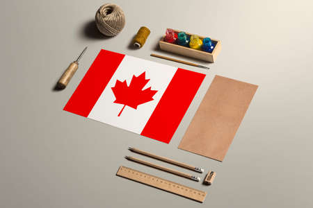 Canada calligraphy concept, accessories and tools for beautiful handwriting, pencils, pens, ink, brush, craft paper and cardboard crafting on wooden table.