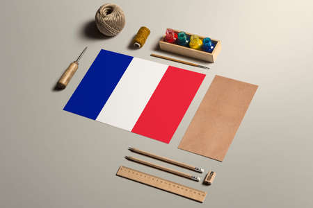 France calligraphy concept, accessories and tools for beautiful handwriting, pencils, pens, ink, brush, craft paper and cardboard crafting on wooden table. 免版税图像