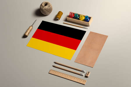 Germany calligraphy concept, accessories and tools for beautiful handwriting, pencils, pens, ink, brush, craft paper and cardboard crafting on wooden table.