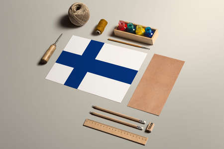 Finland calligraphy concept, accessories and tools for beautiful handwriting, pencils, pens, ink, brush, craft paper and cardboard crafting on wooden table.