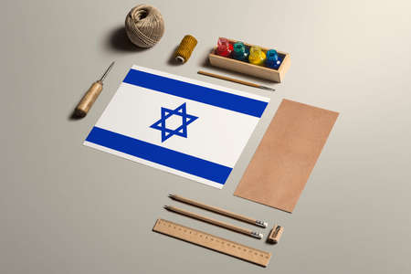 Israel calligraphy concept, accessories and tools for beautiful handwriting, pencils, pens, ink, brush, craft paper and cardboard crafting on wooden table.