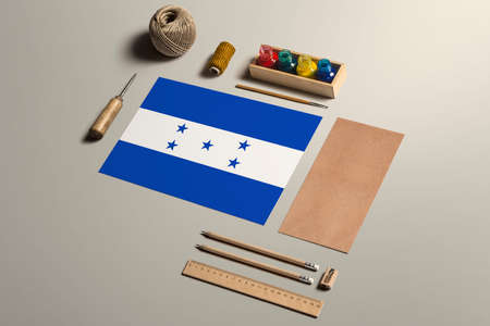 Honduras calligraphy concept, accessories and tools for beautiful handwriting, pencils, pens, ink, brush, craft paper and cardboard crafting on wooden table.