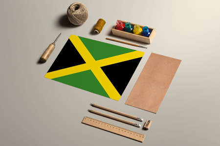 Jamaica calligraphy concept, accessories and tools for beautiful handwriting, pencils, pens, ink, brush, craft paper and cardboard crafting on wooden table. 免版税图像