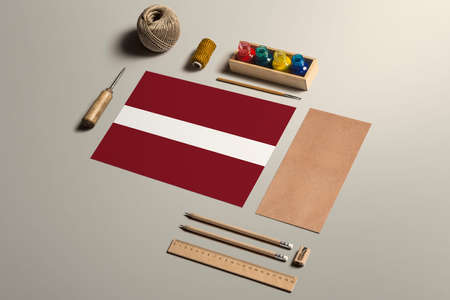 Latvia calligraphy concept, accessories and tools for beautiful handwriting, pencils, pens, ink, brush, craft paper and cardboard crafting on wooden table.