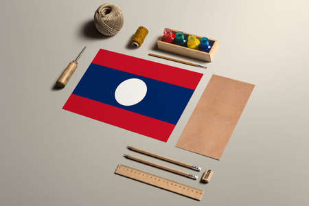 Laos calligraphy concept, accessories and tools for beautiful handwriting, pencils, pens, ink, brush, craft paper and cardboard crafting on wooden table.