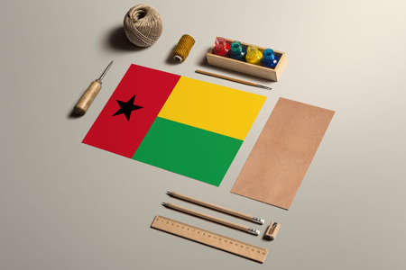 Guinea calligraphy concept, accessories and tools for beautiful handwriting, pencils, pens, ink, brush, craft paper and cardboard crafting on wooden table.