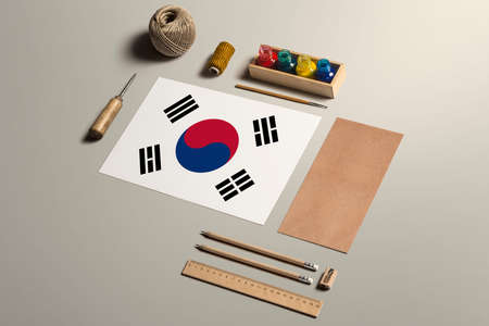 South Korea calligraphy concept, accessories and tools for beautiful handwriting, pencils, pens, ink, brush, craft paper and cardboard crafting on wooden table.