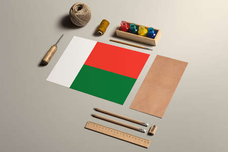 Madagascar calligraphy concept, accessories and tools for beautiful handwriting, pencils, pens, ink, brush, craft paper and cardboard crafting on wooden table.