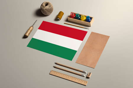 Hungary calligraphy concept, accessories and tools for beautiful handwriting, pencils, pens, ink, brush, craft paper and cardboard crafting on wooden table.