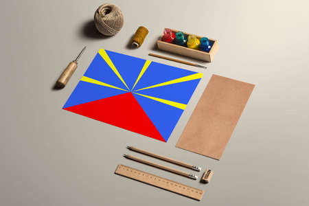 Reunion calligraphy concept, accessories and tools for beautiful handwriting, pencils, pens, ink, brush, craft paper and cardboard crafting on wooden table.