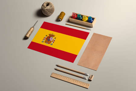 Spain calligraphy concept, accessories and tools for beautiful handwriting, pencils, pens, ink, brush, craft paper and cardboard crafting on wooden table.