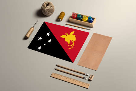 Papua New Guinea calligraphy concept, accessories and tools for beautiful handwriting, pencils, pens, ink, brush, craft paper and cardboard crafting on wooden table. 免版税图像
