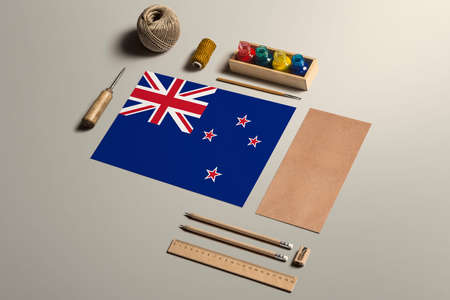 New Zealand calligraphy concept, accessories and tools for beautiful handwriting, pencils, pens, ink, brush, craft paper and cardboard crafting on wooden table.