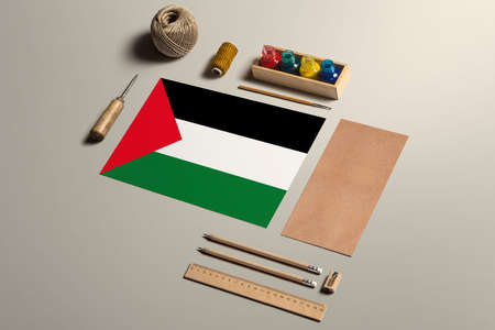 Palestine calligraphy concept, accessories and tools for beautiful handwriting, pencils, pens, ink, brush, craft paper and cardboard crafting on wooden table.