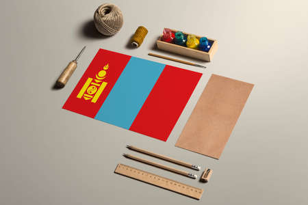 Mongolia calligraphy concept, accessories and tools for beautiful handwriting, pencils, pens, ink, brush, craft paper and cardboard crafting on wooden table.