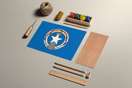 Northern Mariana Islands calligraphy concept, accessories and tools for beautiful handwriting, pencils, pens, ink, brush, craft paper and cardboard crafting on wooden table.