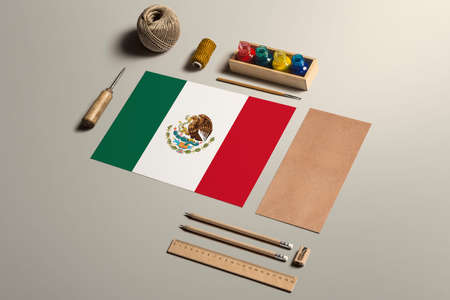 Mexico calligraphy concept, accessories and tools for beautiful handwriting, pencils, pens, ink, brush, craft paper and cardboard crafting on wooden table.