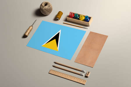 Saint Lucia calligraphy concept, accessories and tools for beautiful handwriting, pencils, pens, ink, brush, craft paper and cardboard crafting on wooden table.