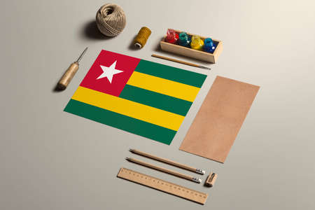 Togo calligraphy concept, accessories and tools for beautiful handwriting, pencils, pens, ink, brush, craft paper and cardboard crafting on wooden table.